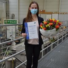 Sofia Engelmeier hält ihre Urkunde und einen Blumenstrauß in der Hand. Im Hintergrund ist die VEGAS-Halle zu sehen.